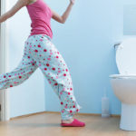 woman running to washroom with toilet paper in hand